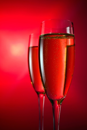 champagne in wineglass on a red background. photo
