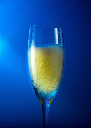 champagne in wineglass on a blue background. photo
