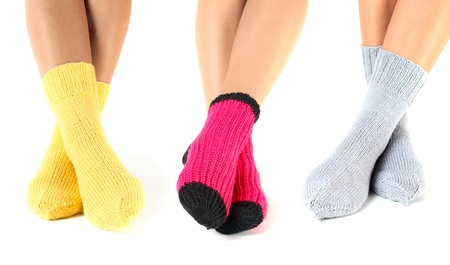 stockings feet: woman legs in woollen socks on a white background.