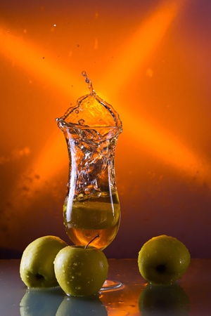 green apples and glass with juice on a glass table. photo