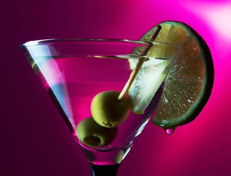 martini with lime and green olives on a purple background. photo