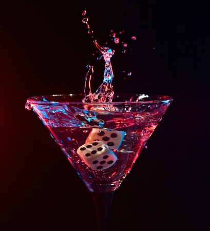 dice fall in a glass with martini.