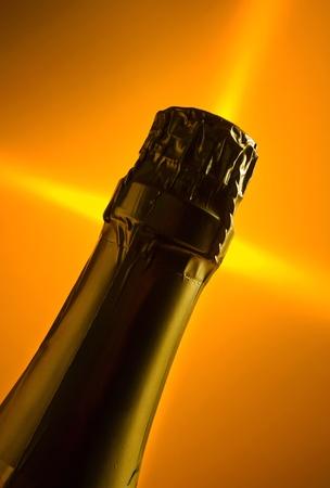 bouteille champagne: Une bouteille de champagne sur un fond orange.