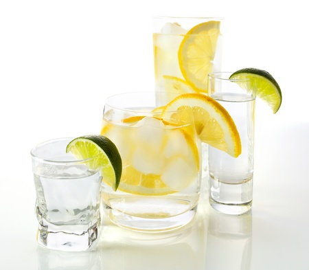 drinks with lemon and lime, shot on reflective white background. photo