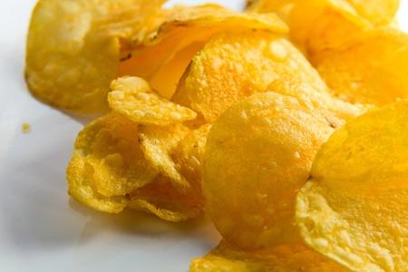 reflexive: fried potato chipson a white reflexive background, macro shot.