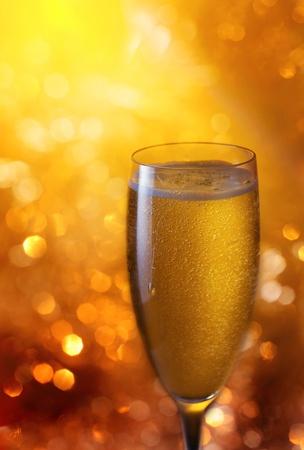 brindisi spumante: champagne in bicchiere su uno sfondo giallo. Archivio Fotografico