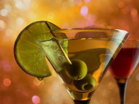 martini with lime and green olives on a orange background. Stock Photo
