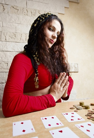The young beautiful gipsy girl predicts the future on cards. Stock Photo - 12117267