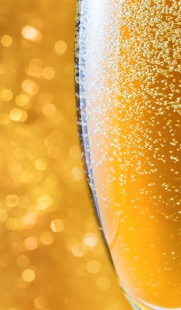 gold flute: champagne in wineglass on a yellow background. Stock Photo