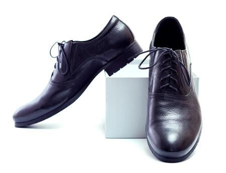 shoe boxes: Nuevos zapatos negros con cordones y caja gris sobre un fondo blanco.
