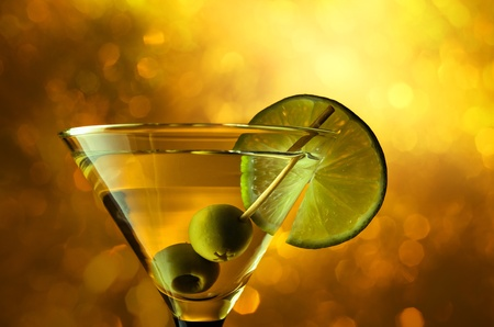martini with lime and green olives on a yellow background.