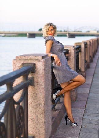 gray clothing:  blond sexy woman in grey dress on a quay. Stock Photo