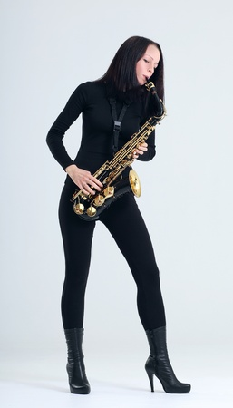 young woman in black with saxophone. photo