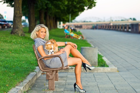 happy blond woman with chihuahua in park. photo
