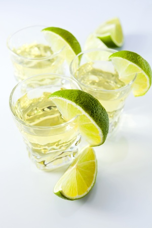 gold tequila with lime on a white reflective background. Stock Photo - 13166994