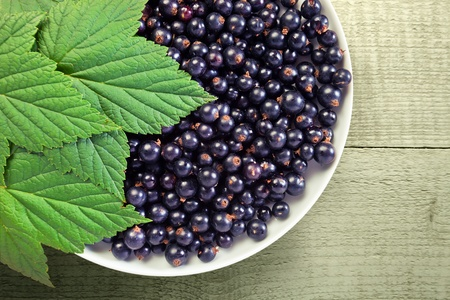 black currant,ripe berries and green leaves on a wood table. photo