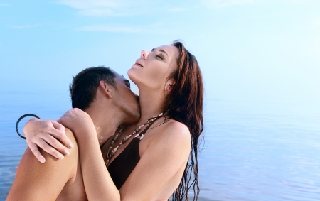 seducing: Young enamoured pair kisses in the sea.