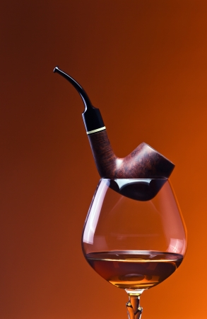 cognac and pipe on a dark background. Stock Photo