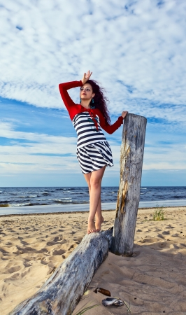 The young woman in striped dress on a beach. photo