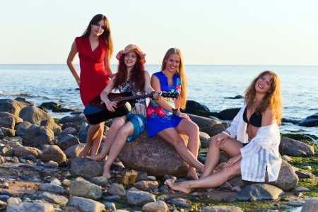 Four girls on seacoast before a sunset photo
