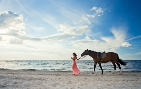 beautiful girl in dress with horse on seacoast photo