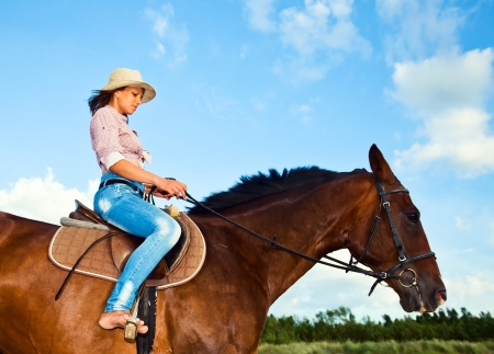 woman horse: young  beautiful girl in hat on a  horse   Stock Photo