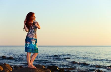 beautiful girl on seacoast before a sunset Stock Photo - 14743001