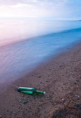 Bottle with the message on sea coast. Long exposure, polarizing filter + ND filter. Movement of waves has blured a background. photo