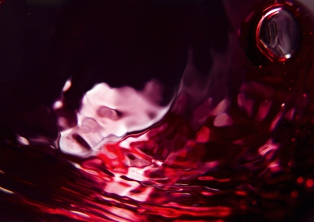 bordeaux: Red wine on a black background, abstract splashing.