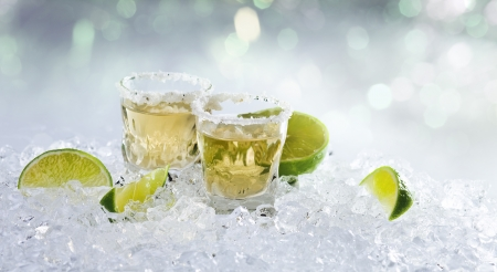 gold tequila with salt and lime on a ice. photo