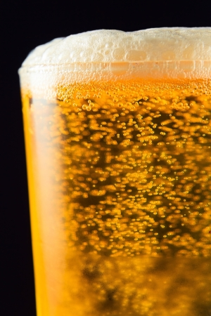 Beer mug with froth over black background photo