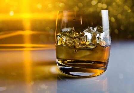 whisky with ice on a reflective background photo