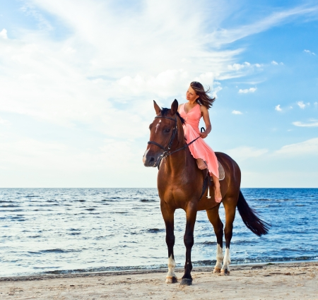 horse riding: beautiful girl in dress with horse on seacoast