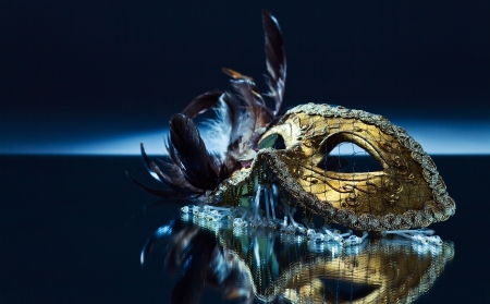 The Venetian mask with feather on a mirror table