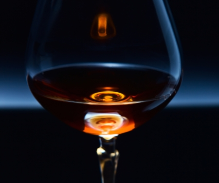 snifter: snifter with brandy on a dark background.