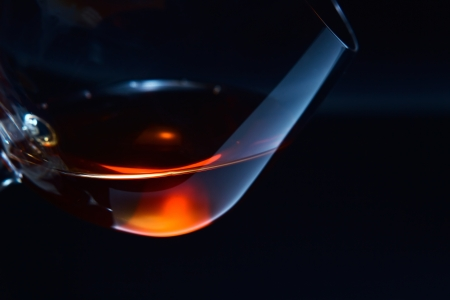 liqueur: snifter with brandy on a dark background.