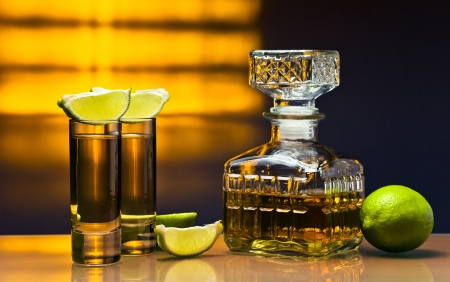 rum: gold tequila and lime on a glass table.