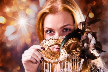 Young beautiful woman with gold venetian mask