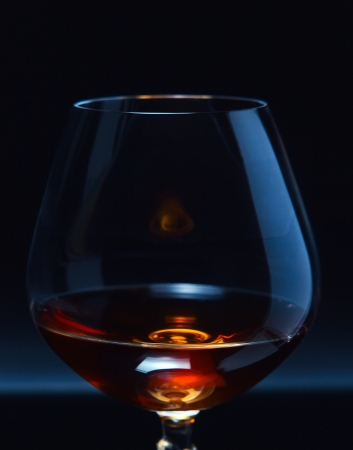 snifter: snifter with brandy on a dark background