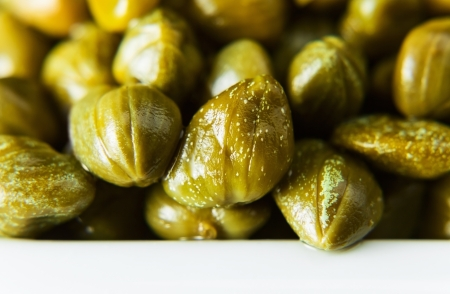 Marinated capers on a white plate , macro shot photo