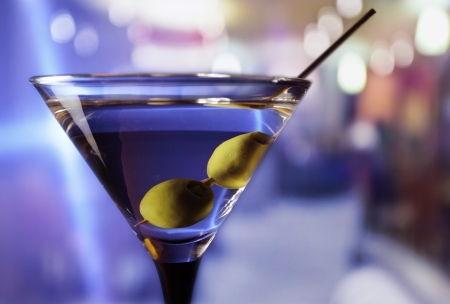 horizontal bar: martini with green olives on a table  in bar Stock Photo
