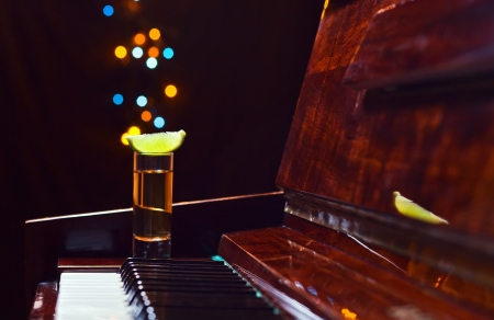 ebony wood: Gratitude for the maestro, glass with tequila on a piano.