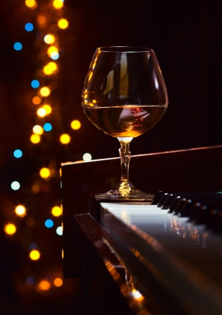 piano closeup: Gratitude for the maestro, snifter with brandy on a piano.