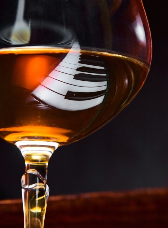 Gratitude for the maestro, snifter with brandy on a piano.