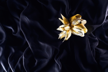 The gold bow on a black textile Stock Photo - 16577344