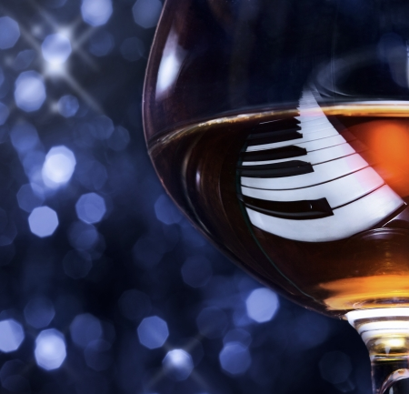 snifter with brandy on a piano, focus on a reflection. Stock Photo