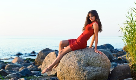beautiful girl in red dress on seacoast  photo