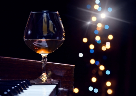 piano closeup:  snifter with  brandy on a piano