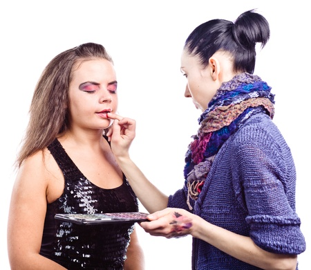 make up artist: make up artist applying make up on actress, isolated on white