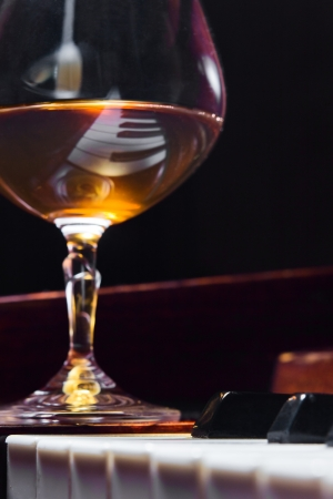 Gratitude for the maestro, snifter with brandy on a piano.  photo